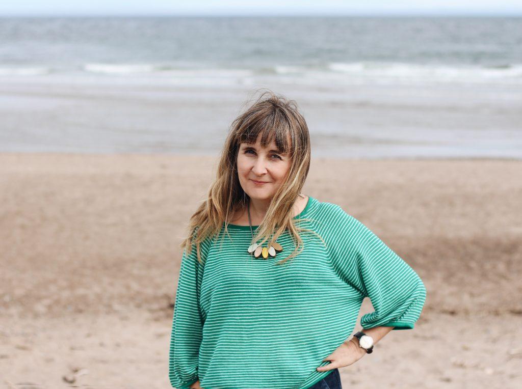 Illustrator Helen Stephens on a beach wearing a green jumper